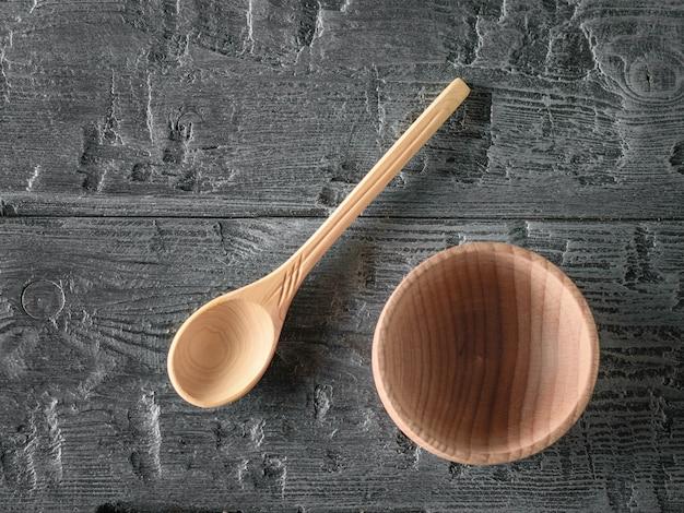 Drewniana miska i łyżka ręcznie na ciemnym drewnianym stole. widok z góry. leżał płasko.
