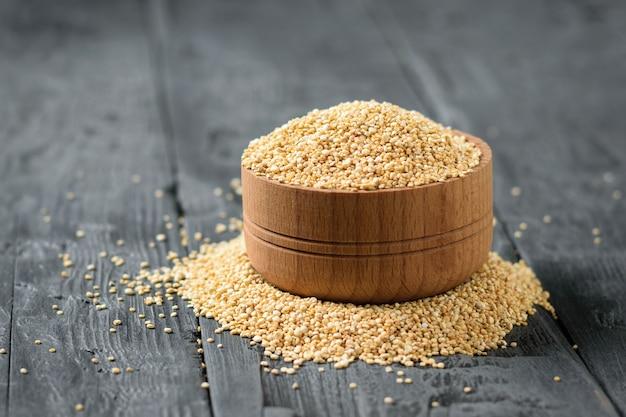 Drewniana miska i stos nasion komosy ryżowej na czarnym drewnianym stole.