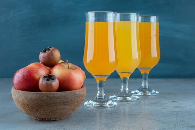 Drewniana miska jabłek ze szklanymi kubkami soku pomarańczowego.
