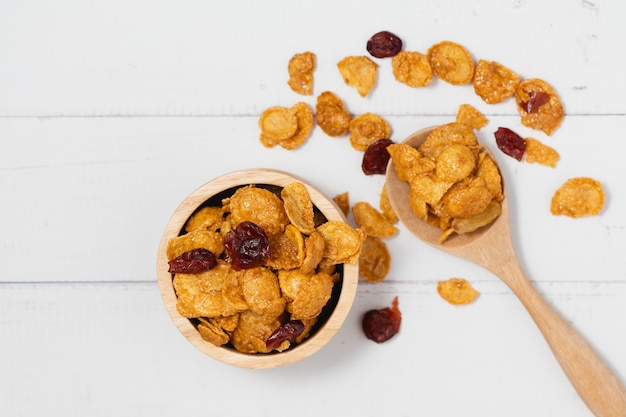 Drewniana miska karmelowych płatków kukurydzianych z rodzynkami na białym tle dla zdrowego odżywiania i koncepcji śniadania