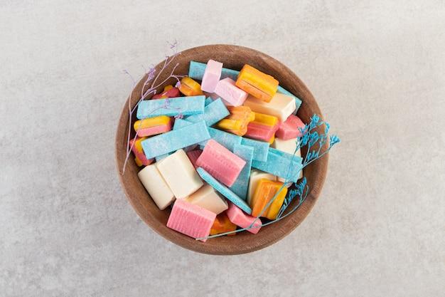 Drewniana miska kolorowych gum aromatycznych na kamiennym stole.