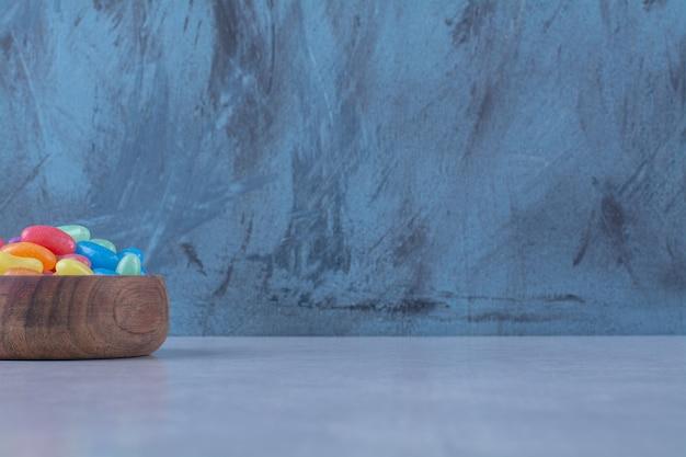 Drewniana miska kolorowych słodkich cukierków z galaretką