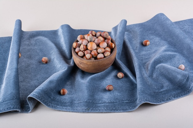 Drewniana miska łuskanych organicznych orzechów laskowych na niebieskim suknem. zdjęcie wysokiej jakości