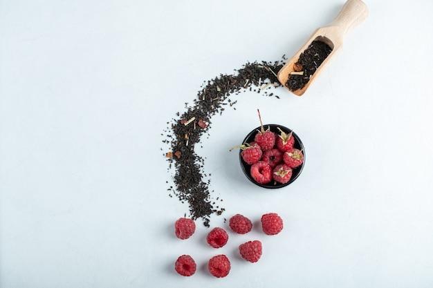 Drewniana miska malin z łyżką czarnej suchej herbaty na kamieniu