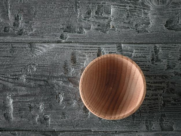 Drewniana miska na ciemnym drewnianym stole. widok z góry. leżał płasko.