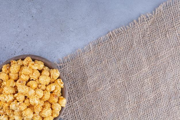 Drewniana miska na kawałku materiału ze stosem karmelowego popcornu na marmurowej powierzchni