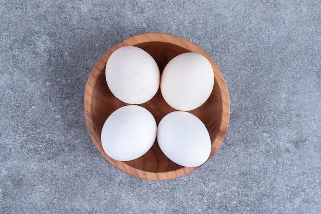 Drewniana miska niegotowanych świeżych jaj na kamieniu.