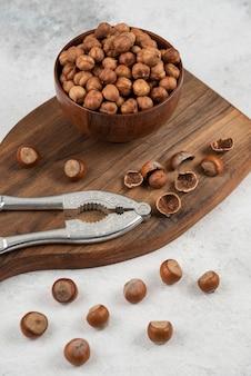 Drewniana miska nieobranych organicznych jąder orzechów laskowych na desce do krojenia.