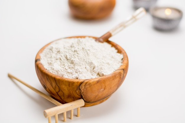 Drewniana miska pełna białej gliny idealna do pielęgnacji ciała