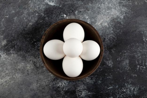Drewniana miska pełna białych, surowych jaj kurzych.