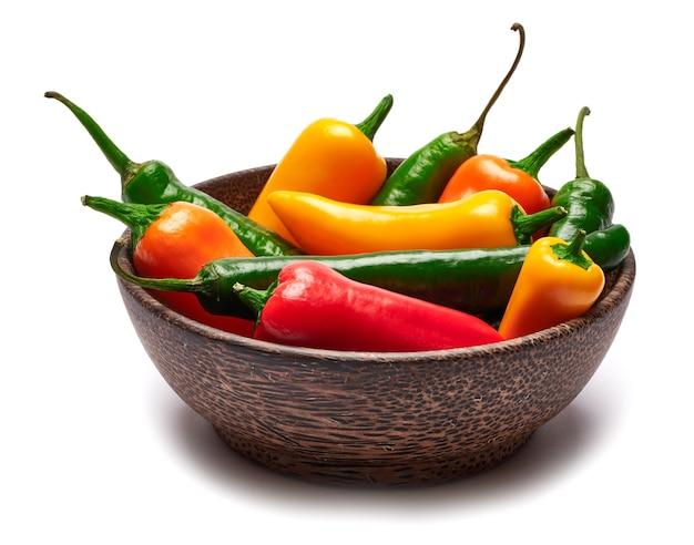 Drewniana miska pełna chili lub papryki słodkiej na białym tle na białej powierzchni
