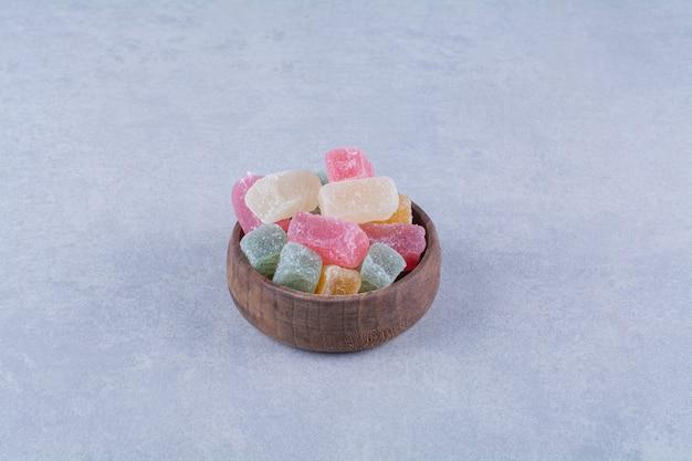 Drewniana miska pełna kolorowych cukierków fasolowych na szarym stole.