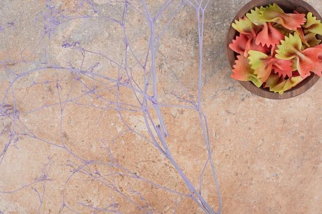 Drewniana miska pełna makaronu muszka na marmurowej przestrzeni.