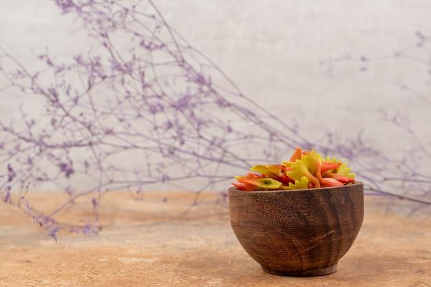 Drewniana miska pełna makaronu muszka na tle marmuru. wysokiej jakości zdjęcie