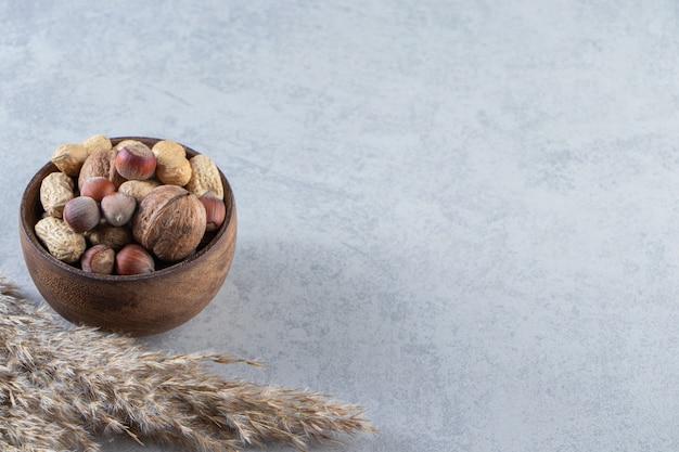 Drewniana miska pełna różnych łuskanych orzechów na tle kamienia.