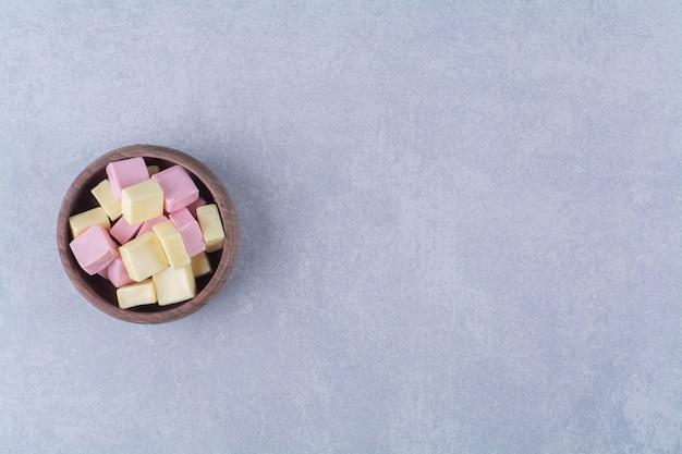 Drewniana miska pełna różowego słodkiego cukierka pastila.