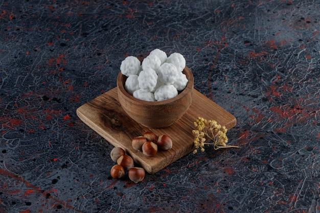 Drewniana miska pełna słodkich białych cukierków ze zdrowymi orzechami na ciemnym stole.