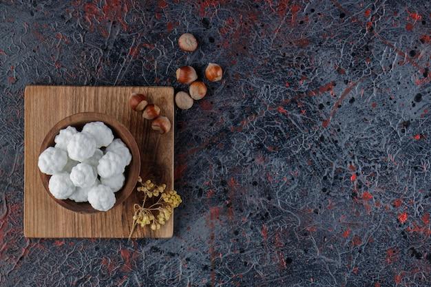 Drewniana miska pełna słodkich białych cukierków ze zdrowymi orzechami na ciemnym tle