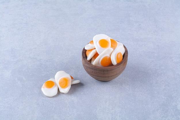 Drewniana miska pełna słodkich jajek smażonych w galarecie na szarym stole.