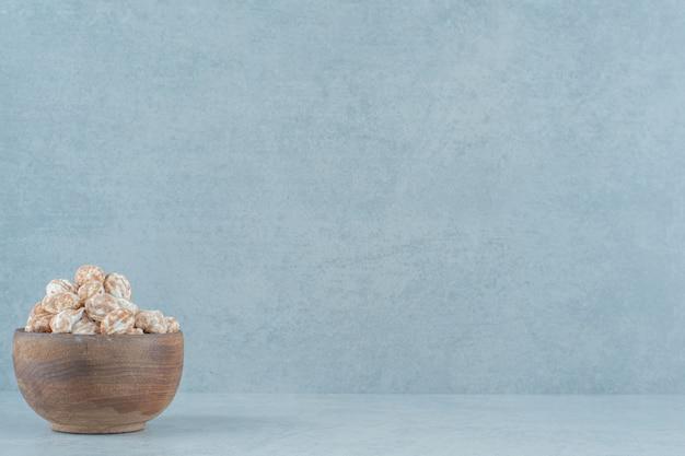 Drewniana miska pełna słodkich pysznych pierników na białej powierzchni