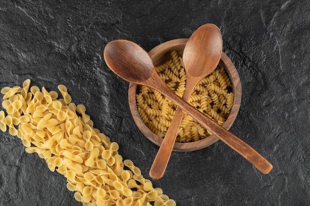 Drewniana miska pełna surowego makaronu girandole .