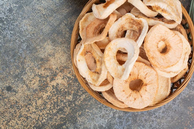 Drewniana miska pełna zdrowego suszonego jabłka na marmurowym tle. wysokiej jakości zdjęcie
