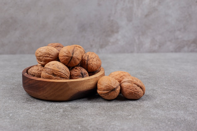Drewniana miska pełna zdrowych orzechów włoskich w twardych łupinach