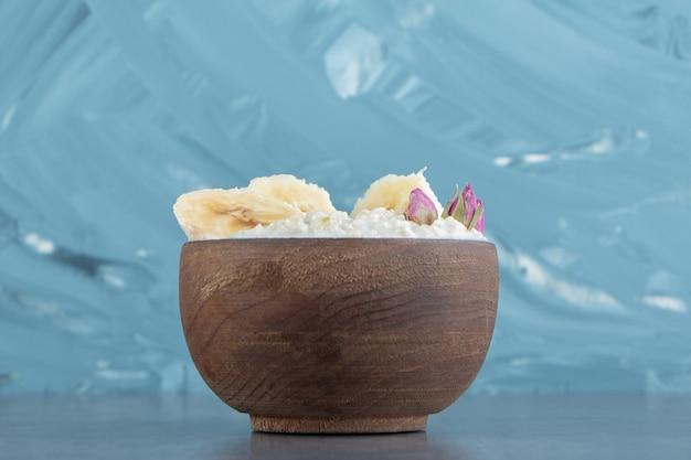 Drewniana miska płatków owsianych z kawałkami banana.