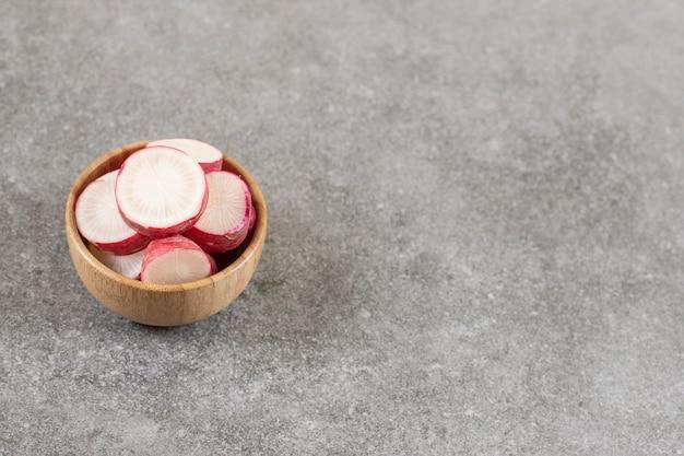 Drewniana miska pokrojonej w plasterki czerwonej rzodkwi na marmurowej powierzchni.