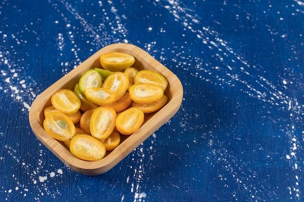 Drewniana miska pokrojonych w plasterki świeżych owoców kumkwatu na marmurowej powierzchni