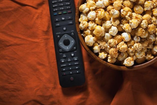 Drewniana miska popcornu i pilota.