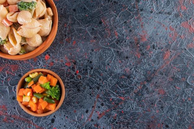 Drewniana miska pysznego makaronu z muszelek i mini sałatki na marmurowej powierzchni.