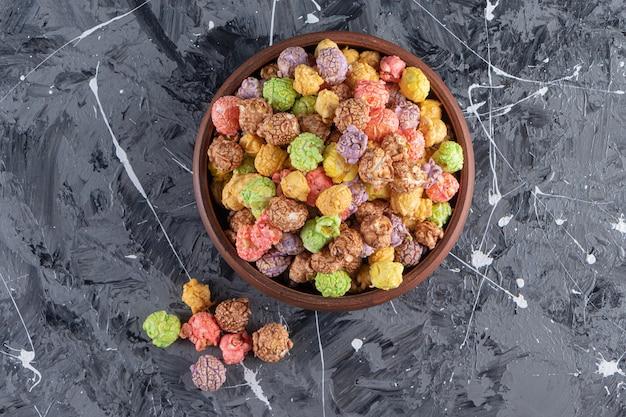 Drewniana miska pysznych kolorowych popcornów na marmurowym stole.