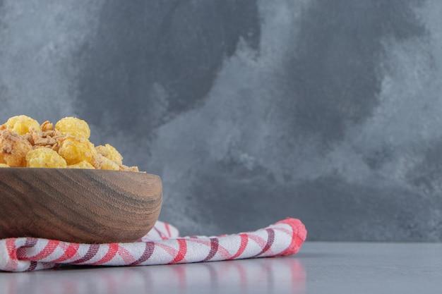 Drewniana miska pysznych zdrowych płatków na obrusie
