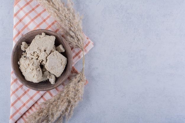 Drewniana miska smacznej chałwy słonecznikowej na kamieniu.