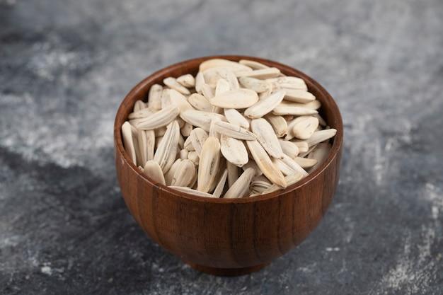 Drewniana miska smażonych nasion słonecznika na kamiennej powierzchni