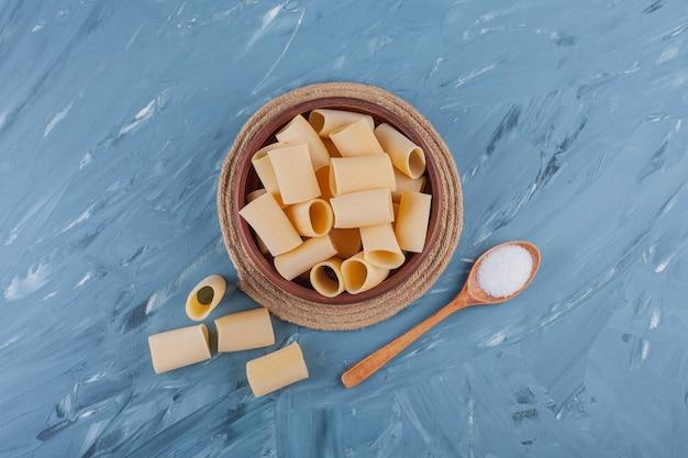 Drewniana miska suchego surowego makaronu rurowego na niebieskim stole.