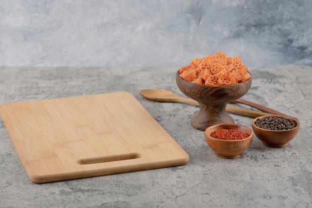 Drewniana miska surowego makaronu i przypraw na marmurowym tle