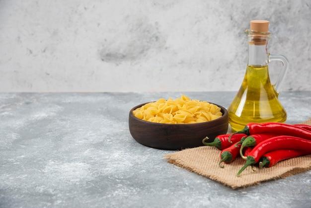 Drewniana miska surowego makaronu z czerwoną papryczką chili i olejem na marmurze.
