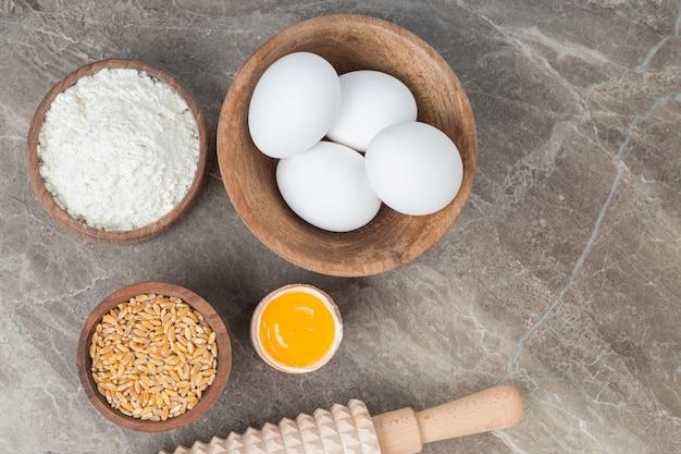 Drewniana miska surowych jajek, mąki i jęczmienia na marmurowej powierzchni.