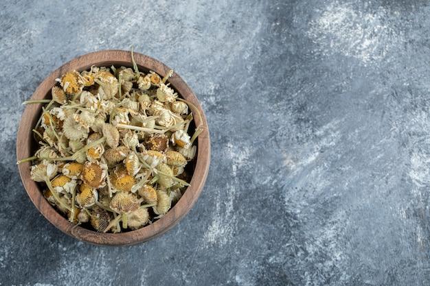 Drewniana miska suszonego rumianku na marmurowym stole.