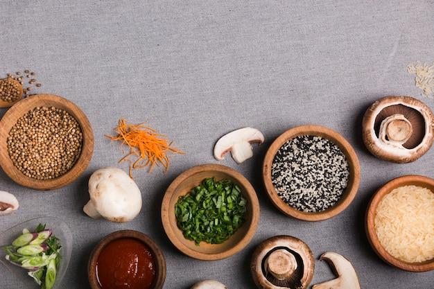 Drewniana miska szczypiorku; nasiona kolendry; sos; grzyb; ziarna ryżu i startej marchwi na szarym obrusie lnianym