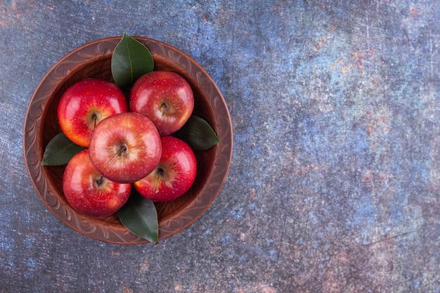 Drewniana miska z błyszczącymi czerwonymi jabłkami na kamiennym tle.