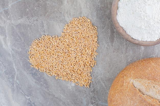 Drewniana miska z chlebem i ziarnami owsa na marmurowej powierzchni