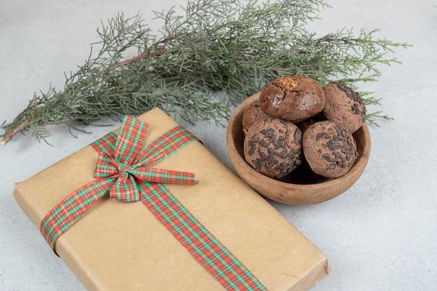 Drewniana miska z czekoladowymi ciasteczkami z prezentem świątecznym.