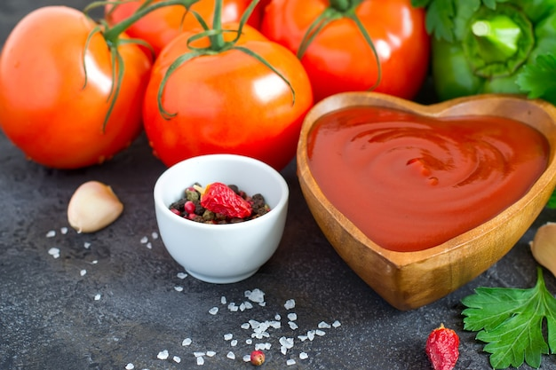 Drewniana miska z keczupem pomidorowym i składnikami, selektywne skupienie
