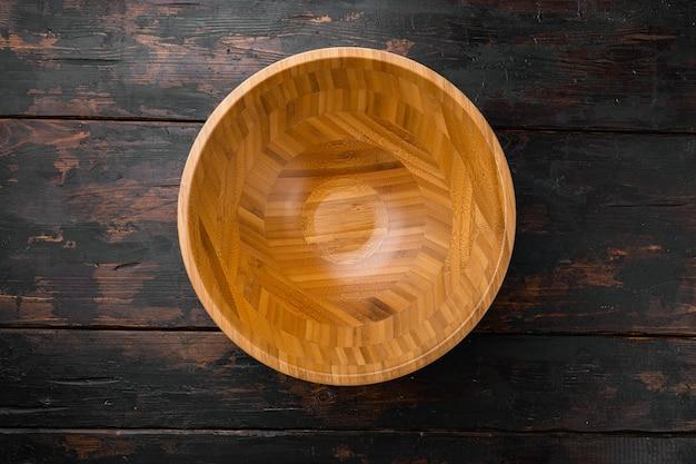 Drewniana miska z kopią miejsca na tekst lub jedzenie, widok z góry płasko leżał, na starym ciemnym drewnianym stole w tle