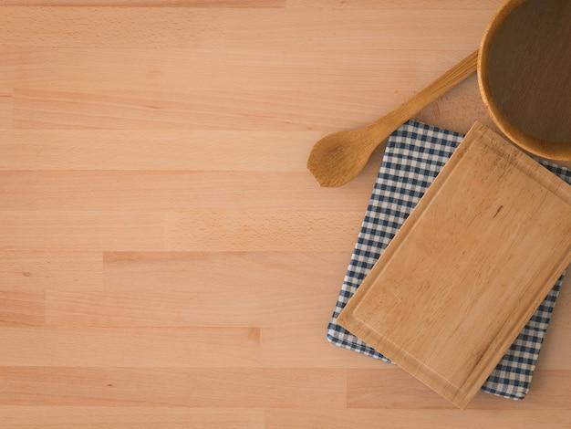 Drewniana miska z łyżką i deską do krojenia na drewnianym tle