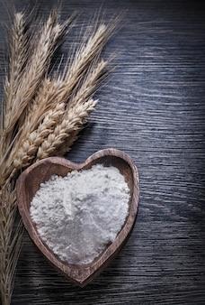 Drewniana miska z mąką z dojrzałych kłosów żytniej pszenicy