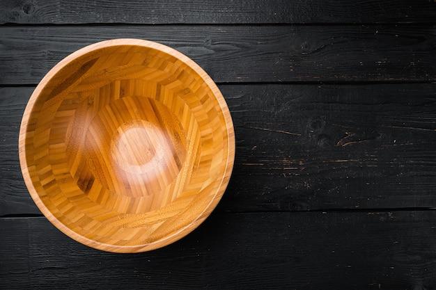 Drewniana miska z miejscem na kopię na tekst lub jedzenie, widok z góry płasko leżący, na czarnym drewnianym stole w tle